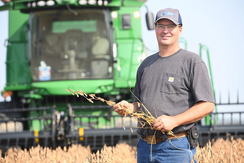 Jeff stands in a soybean field in front of his combine.
