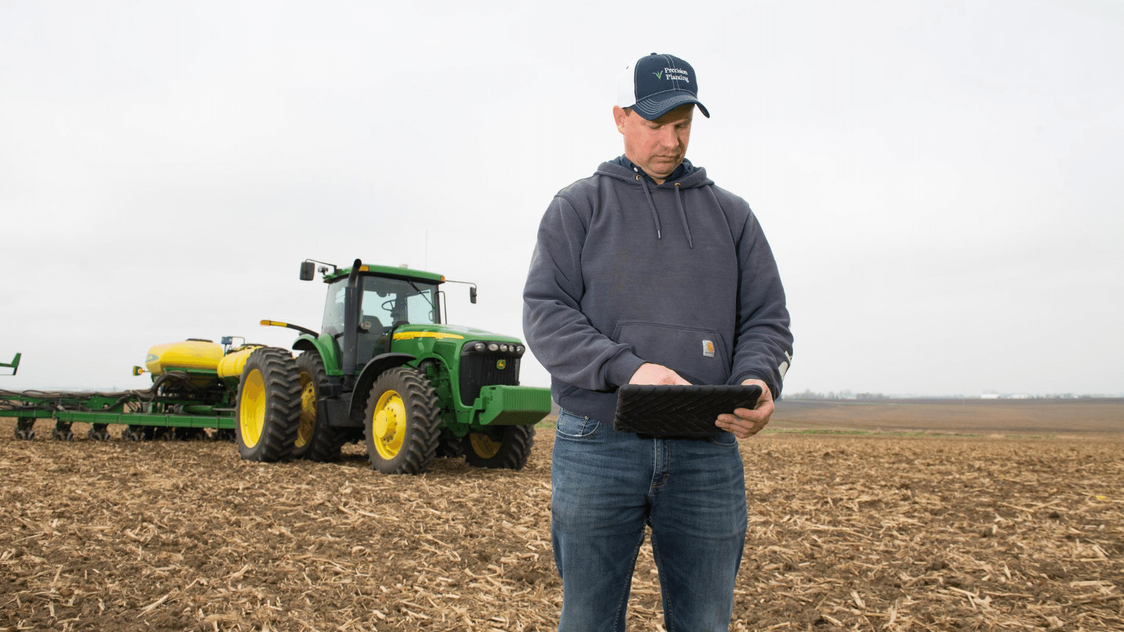 A farmer stands in his field looking at data on his tab