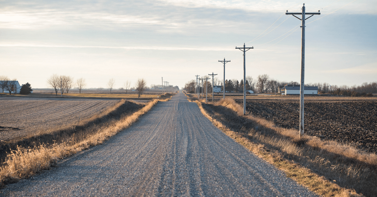 A gravel country road winds past a farmstead.