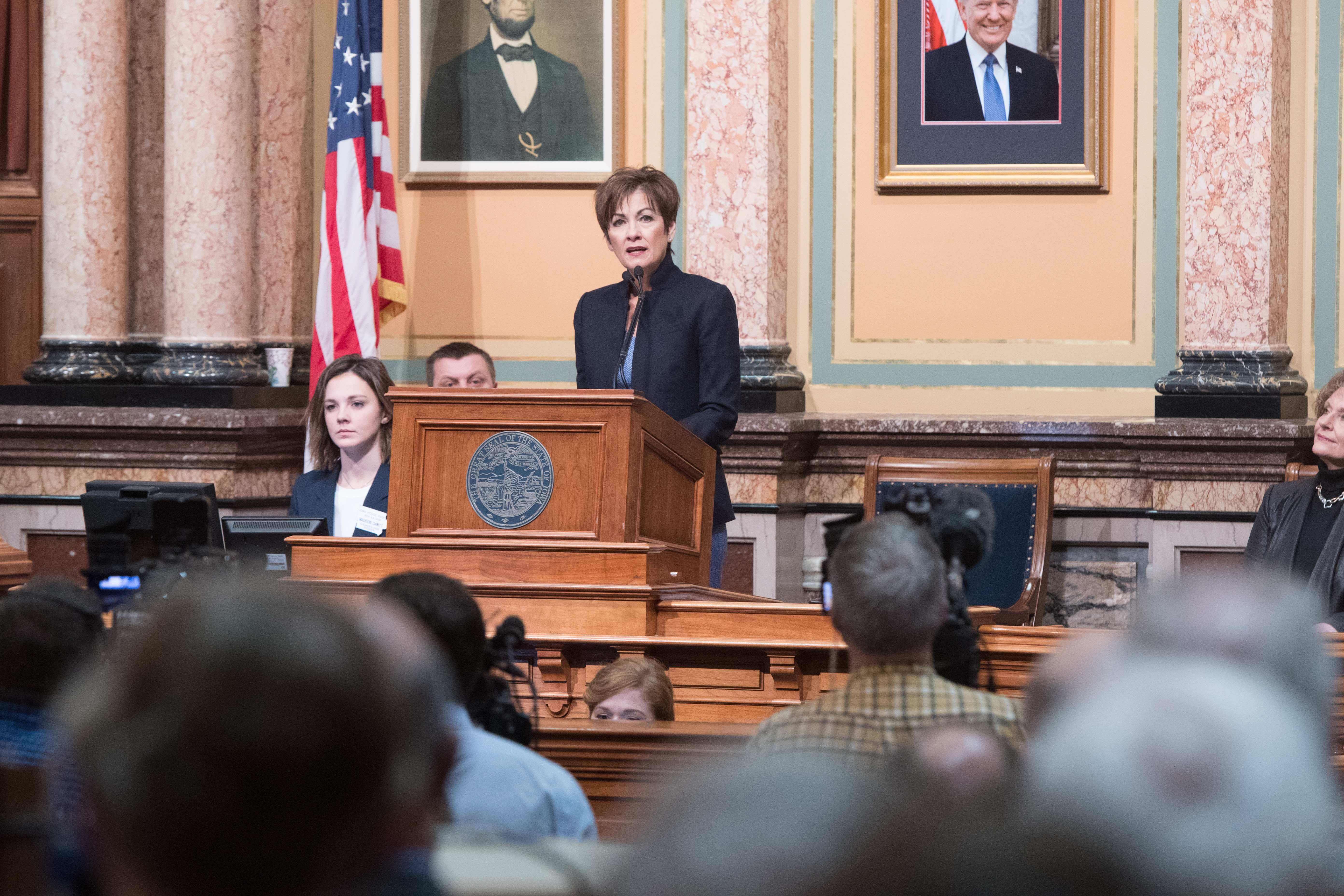 Governor Kim Reynolds speaks at a podium inside the Sta