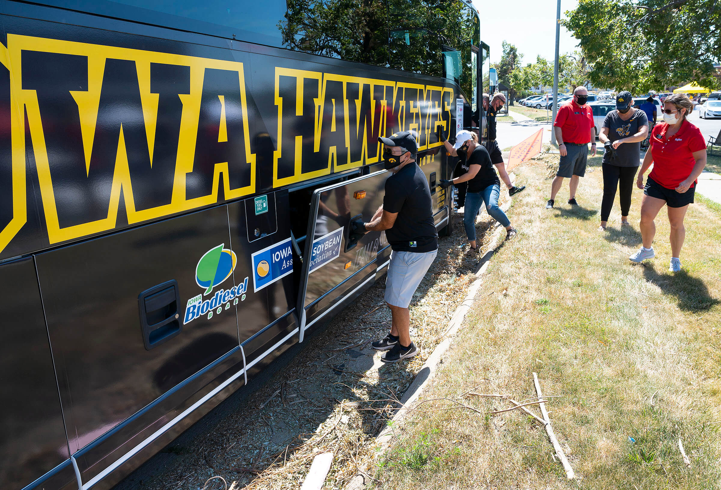 Iowa Hawkeye team bus with people outside of it wearing