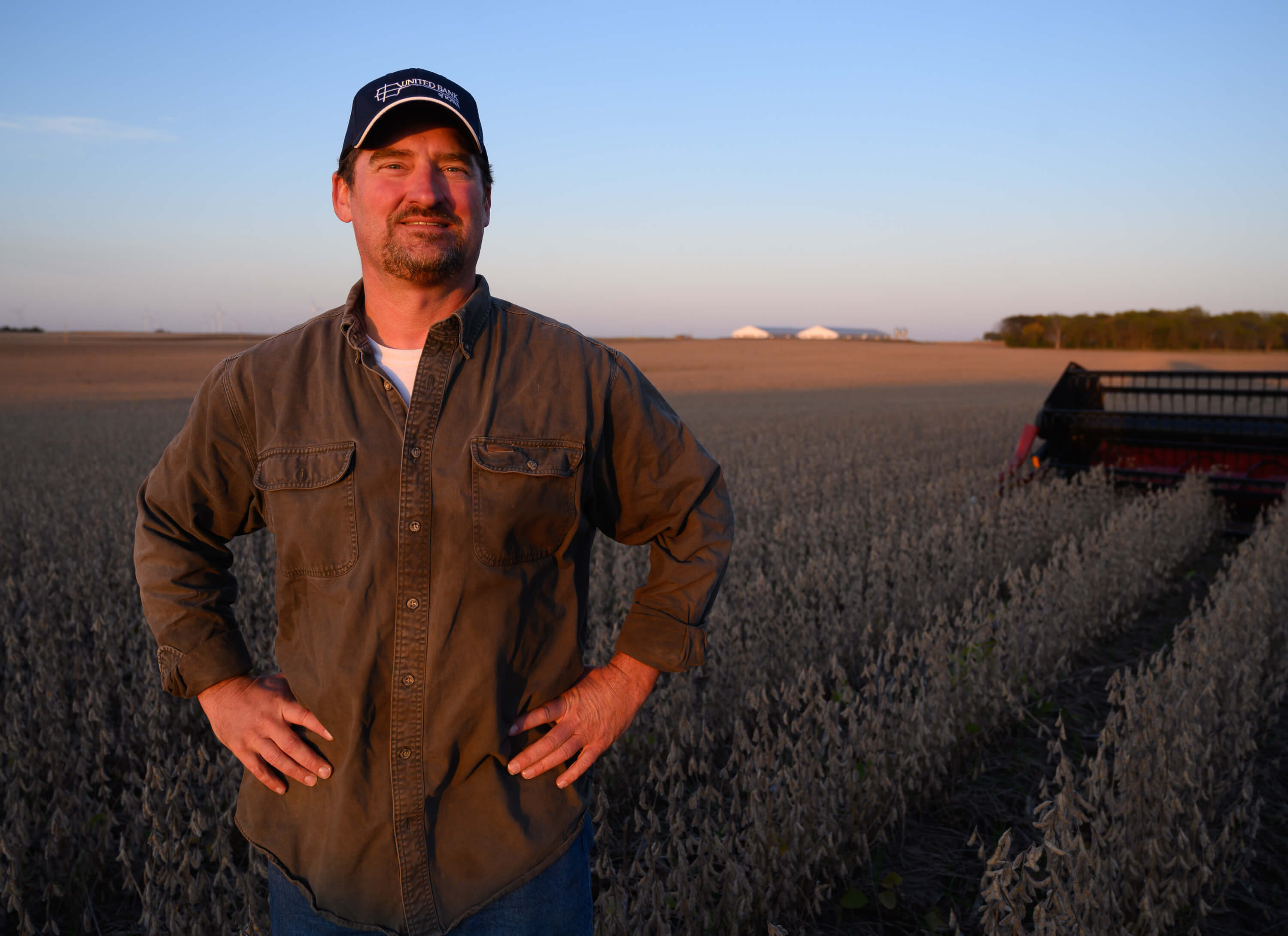 Tim Bardole poses in front of soybean field at harvest