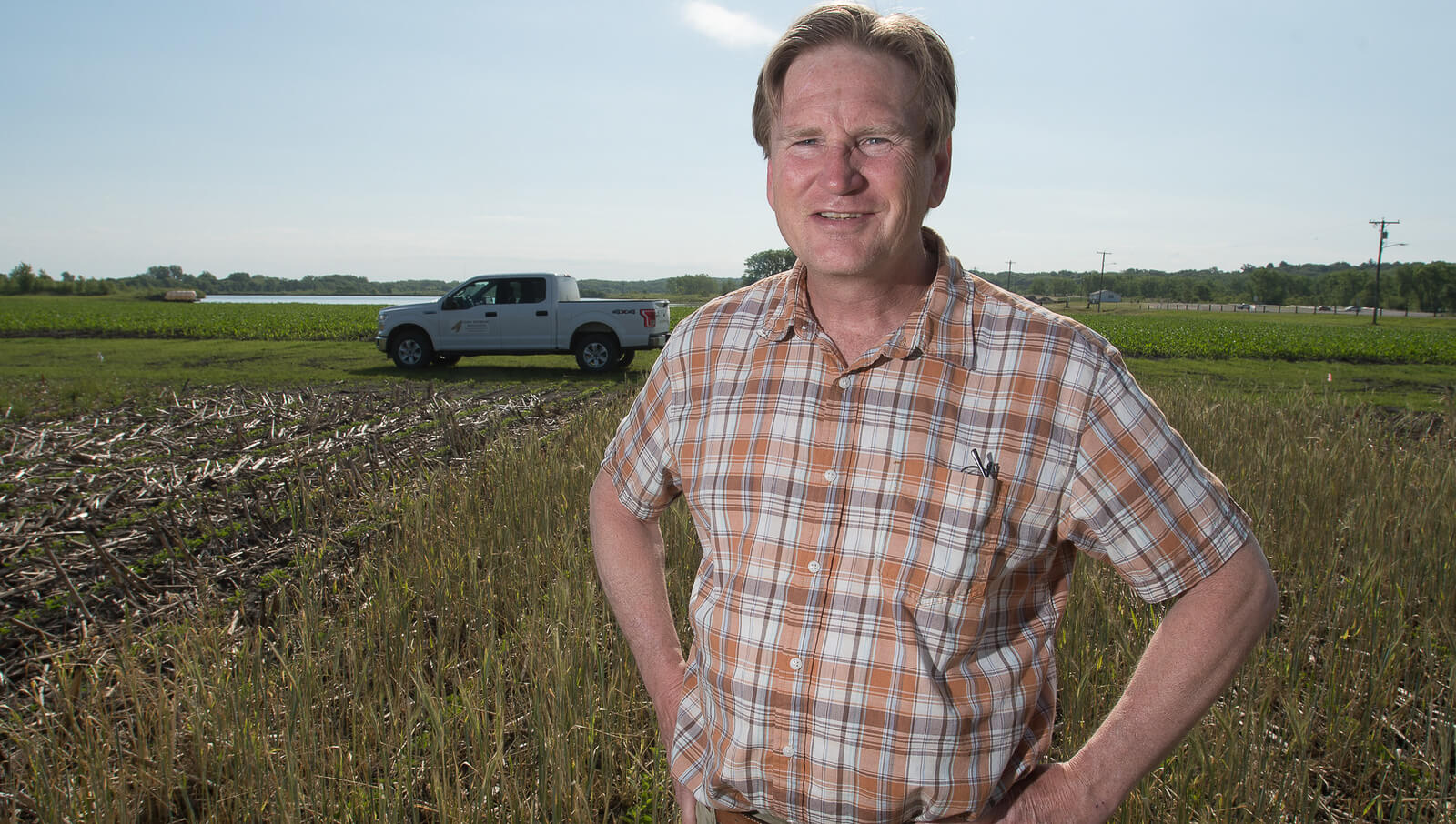 Scott Nelson poses in front of farm field with pickup i