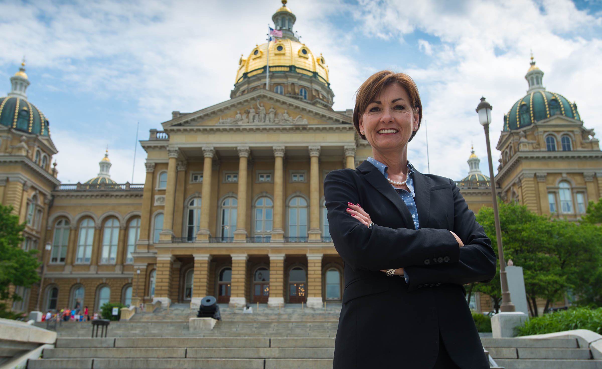 Governor Reynolds poses in front of the state capitol b