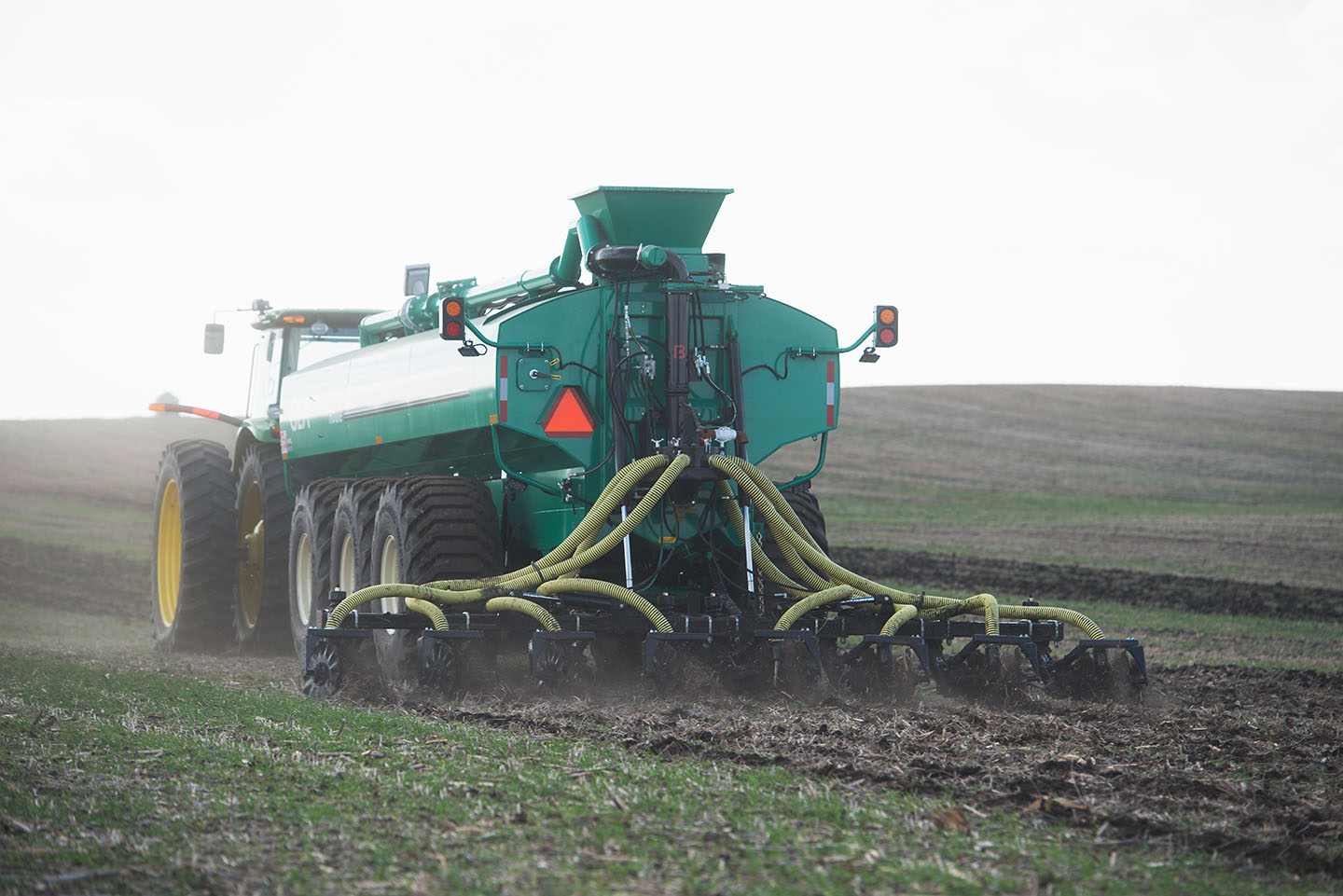 A farmer operates a manure spreader in one of their fie