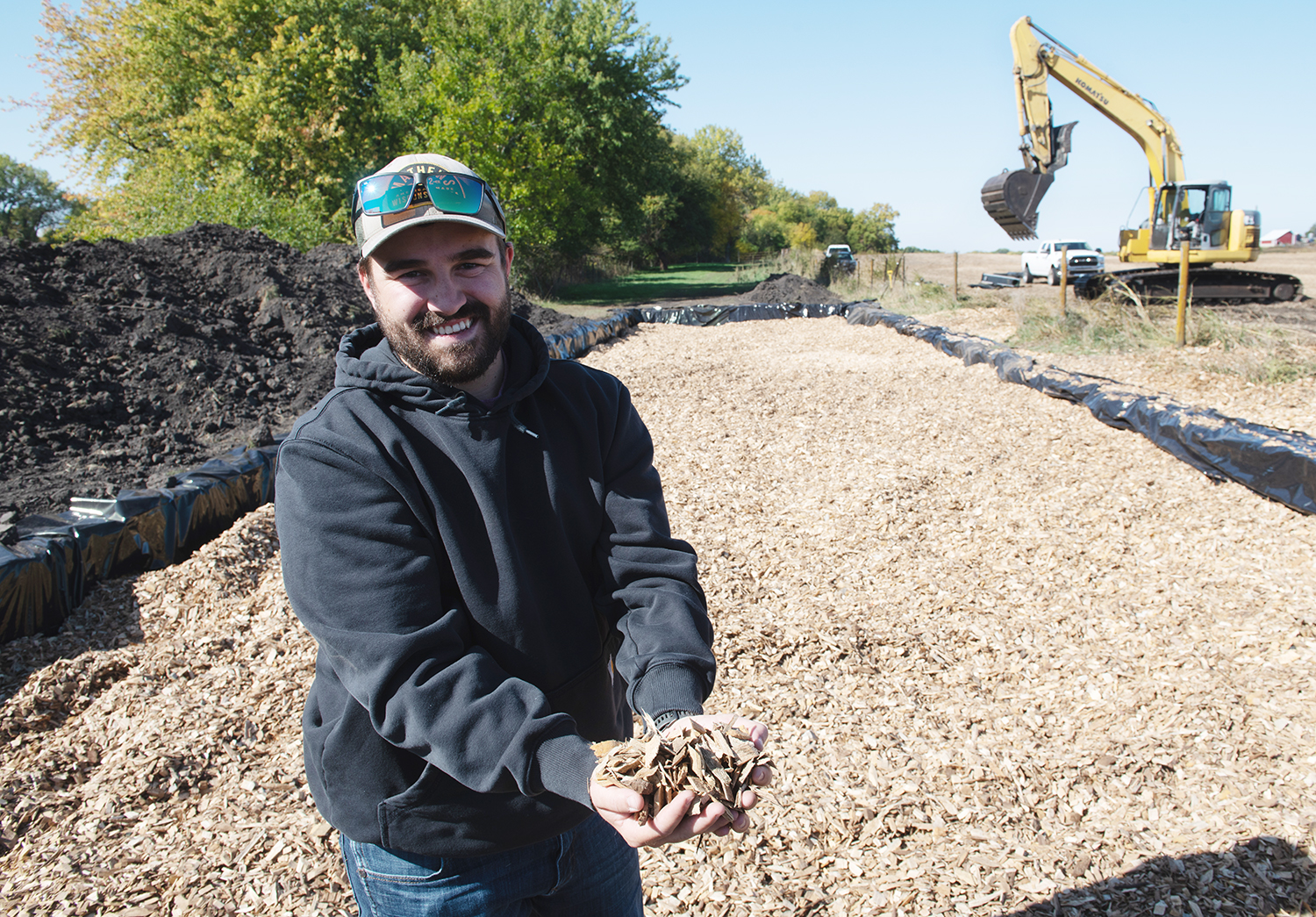 Corey McKinney holds wood chips that will be used in a